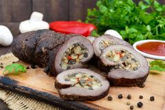 Meatloaf ο ρόλος γέμισε με τα μανιτάρια, το γλυκό πιπέρι και τη σάλτσα ντοματών σε ένα σκοτεινό ξύλινο υπόβαθρο Στοκ Εικόνες