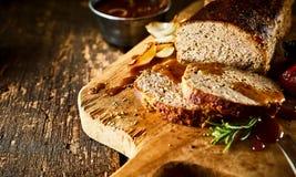 Meatloaf cortado na placa de madeira com ervas e molho fotografia de stock