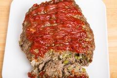 Meatloaf cozido fresco na placa de corte branca Imagem de Stock Royalty Free