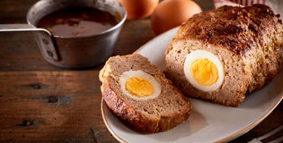 Meatloaf with egg. Meatloaf baked with egg inside sliced on white dish on wooden rustic table Royalty Free Stock Images