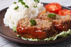 Meatloaf with rice and tomatoes on a plate close-up Stock Image