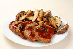 Meatloaf with sauce. A platter of sliced meatloaf with sliced potatoes Stock Photos