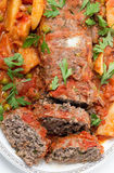 Meatloaf serving dish vertical. Homemade meatloaf baked in tomato sauce with peas and potatoes Royalty Free Stock Images