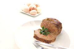 Meatloaf on a white plate. Eggs and onion in the background Royalty Free Stock Image
