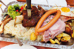 Meatplatter with sauerkraut,roasted potatoes and fried egg Royalty Free Stock Images