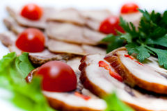 Meats decorated with cherry tomatoes Stock Photo