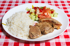 Meats, rice and vegetables on white plate. Meat and rice Royalty Free Stock Images