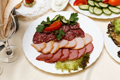 Meats, salami, carbonate on white dish Royalty Free Stock Images