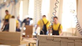 Meblarscy pracownicy fabryczni w żółtych kombinezonach zbierają meble, Meblarska manufaktura zdjęcie wideo