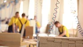 Meblarscy pracownicy fabryczni w żółtych kombinezonach zbierają meble, meblarska manufaktura, przemysłowy wnętrze, mała głębia zdjęcie wideo
