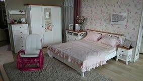 Meblarska sala wystawowa: nowożytna sypialnia z różowym kołysa krzesłem Zdjęcie Royalty Free