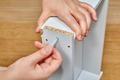 Meblarski asembler stawia plastikowej szpilki w dziurę na powierzchni drewniany kreślarz z jego kciukiem z inną ręką, zdjęcia stock