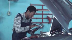 Mecánico africano que se coloca de mirada de un motor de coche almacen de video