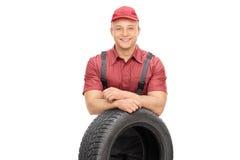 Mecánico alegre que se coloca detrás de un neumático de coche Fotografía de archivo