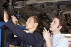 Mecánico And Apprentice Working en el coche junto Fotos de archivo libres de regalías