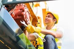 Mecánico asiático que repara el vehículo de la construcción Fotos de archivo