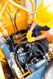 Mecánico asiático que repara el vehículo de la construcción Imágenes de archivo libres de regalías