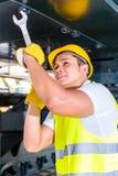 Mecánico asiático que repara el vehículo de la construcción Imagen de archivo libre de regalías