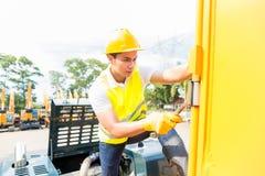 Mecánico asiático que repara el vehículo de la construcción Foto de archivo libre de regalías
