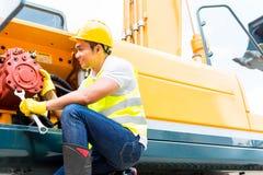 Mecánico asiático que repara el vehículo de la construcción Foto de archivo