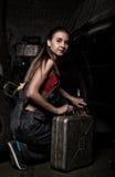 Mecánico atractivo de la muchacha que se sienta al lado de la máquina y que sostiene una poder de gasolina concepto descolorido d Foto de archivo