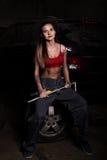 Mecánico atractivo de la muchacha que se sienta en un neumático que sostiene una llave en su mano concepto descolorido de la vida Imagenes de archivo