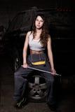 Mecánico atractivo de la muchacha que se sienta en un neumático que sostiene una llave en su mano concepto descolorido de la vida Foto de archivo