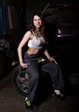 Mecánico atractivo de la muchacha que se sienta en un neumático que sostiene una llave en su mano concepto descolorido de la vida Imagen de archivo