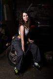 Mecánico atractivo de la muchacha que se sienta en un neumático que sostiene una llave en su mano concepto descolorido de la vida Foto de archivo libre de regalías