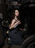 Mecánico atractivo de la muchacha que se sienta en un neumático que sostiene una llave en su mano concepto descolorido de la vida Fotografía de archivo