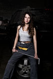 Mecánico atractivo de la muchacha que se sienta en un neumático que sostiene una llave en su mano concepto descolorido de la vida Imágenes de archivo libres de regalías