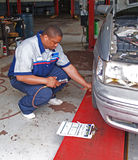 Mecánico auto que realiza el examen de la presión de neumático Foto de archivo