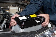 Mecánico auto que substituye la batería de coche Fotos de archivo libres de regalías