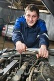 Mecánico automotor feliz en el trabajo con la llave Imagen de archivo libre de regalías