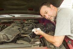 Mecánico Checking The Oil en un camión viejo Foto de archivo