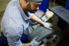 Mecánico con el neumático Foto de archivo libre de regalías