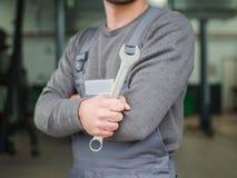 Mecánico con llaves en el primer del taller contra la pared Fotografía de archivo libre de regalías