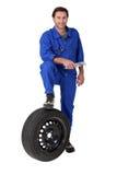 Mecánico con un neumático de repuesto fotos de archivo libres de regalías