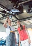 Mecánico de automóviles confiable que comprueba el coche de una mujer en un taller de reparaciones moderno fotos de archivo libres de regalías