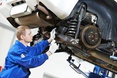 Mecánico de automóviles en el trabajo de la reparación de la suspensión del coche