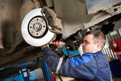 Mecánico de automóviles en el trabajo de la reparación de la suspensión del coche imagen de archivo