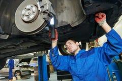 Mecánico de automóviles en las zapatas del coche eximining Foto de archivo libre de regalías