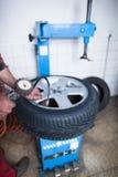 Mecánico de automóviles en un garaje que controla la presión de aire en un neumático Fotos de archivo