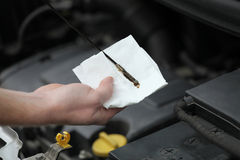 Mecánico de automóviles que comprueba la varilla graduada del aceite de motor en coche Fotos de archivo