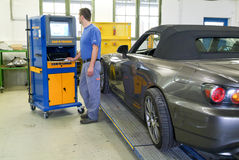 Mecánico de automóviles que hace la alineación de rueda en su garaje Imagenes de archivo