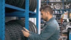 Mecánico de automóviles sonriente del hombre que lleva el nuevo neumático en la tienda del neumático que elige para su coche almacen de metraje de vídeo