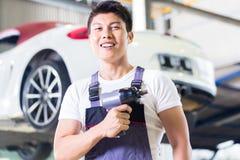Mecánico de coche con la herramienta en taller auto chino asiático imagen de archivo libre de regalías