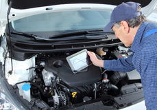 Mecánico de coche con la tableta de diagnóstico del equipo fotografía de archivo libre de regalías