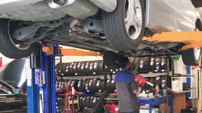 Mecánico de coche en el trabajo en el garaje almacen de metraje de vídeo
