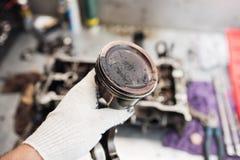 Mecánico de coche en garaje con el pistón viejo del motor de coche Imagenes de archivo